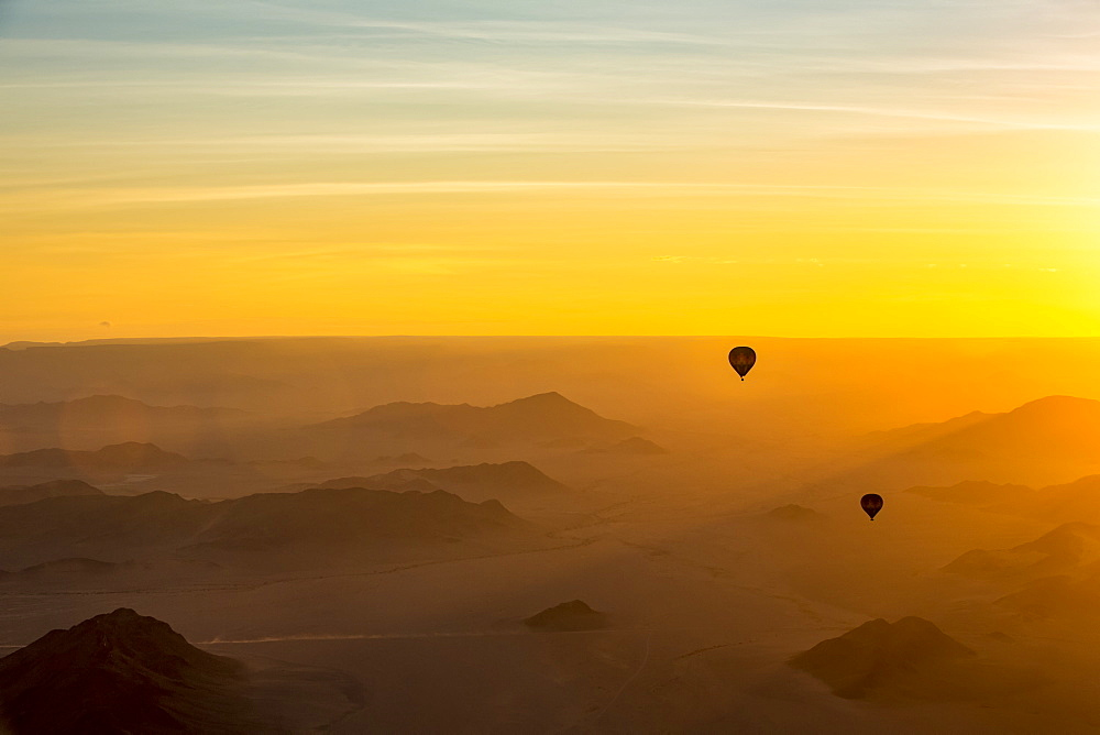 Silhouette of hot air balloons in the golden sky over the sand dunes at sunrise in the Namib Desert, Sossusvlei, Hardap Region, Namibia
