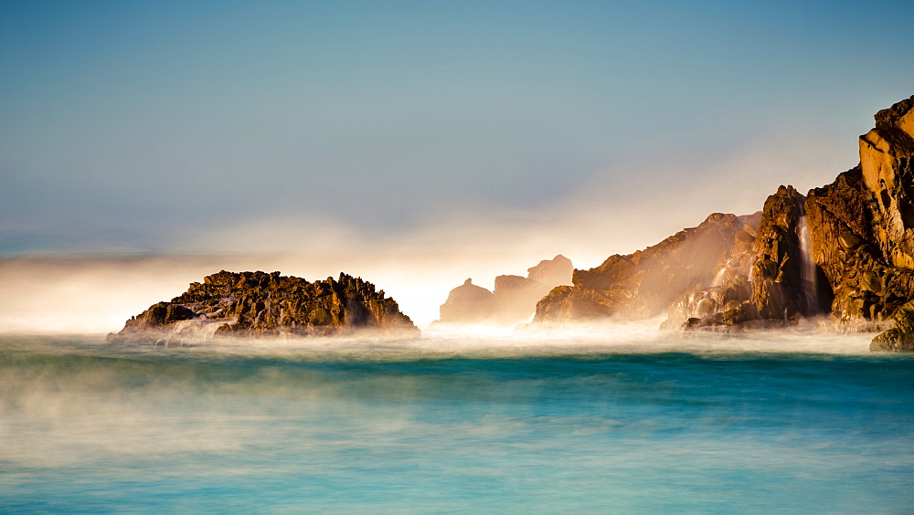 Mist over the turquoise water along the rugged coastline, Big Sur, California, United States of America