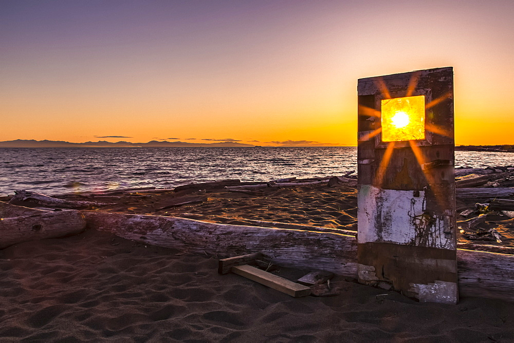 A sunburst shines bright through the window of a weathered, wooden door propped up on Iona beach, Richmond, British Columbia, Canada