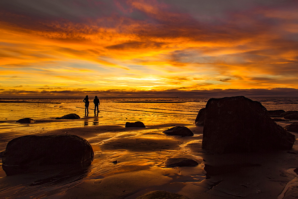 Silhouette of two people standing on Wreck Beach with an orange glow at sunset, Vancouver, British Columbia, Canada - 1116-48782