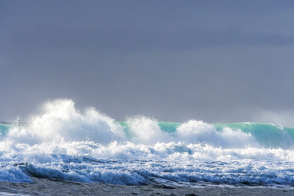 Sunlight shines on a wave under a cloudy sky along the Oregon coast, Lincoln City, Oregon, United States of America