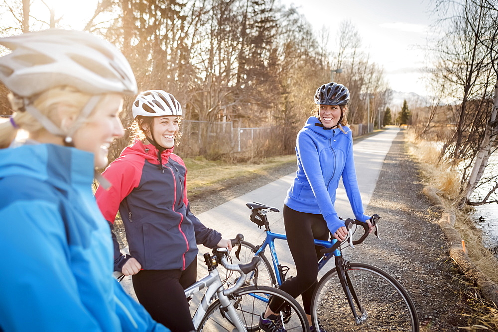 Three young women on their bicycles on a trail at sunrise, Anchorage, Alaska, United States of America