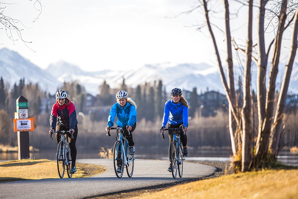 Three young women riding their bicycles on a trail along the water's edge, Anchorage, Alaska, United States of America