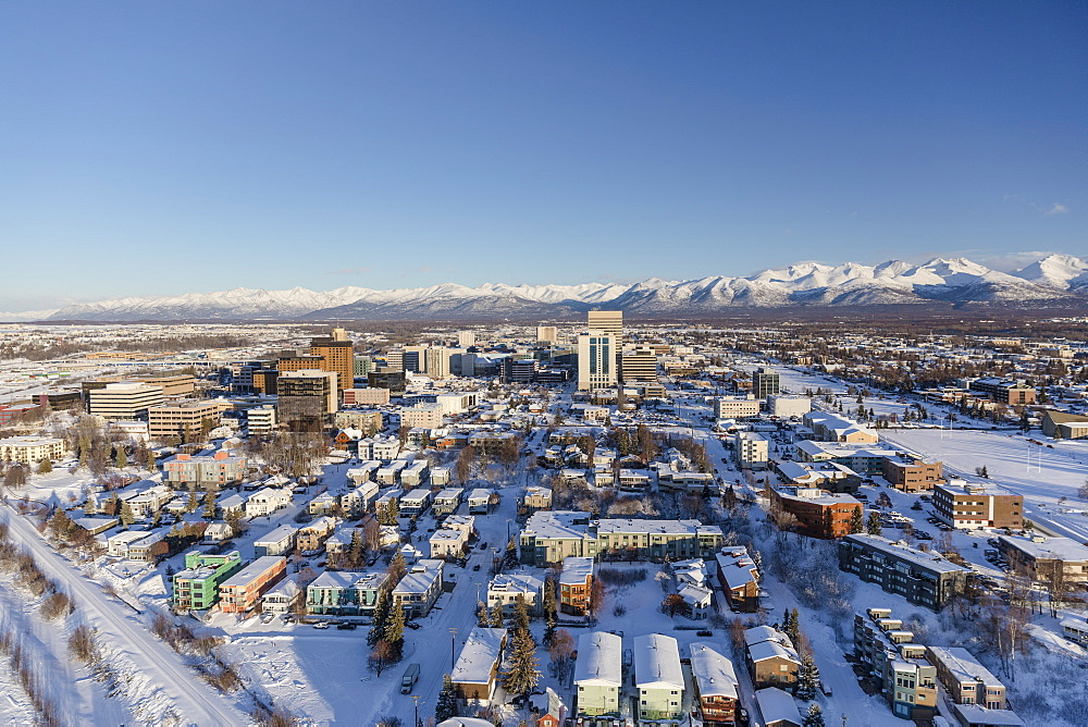 Aerial view of snow covering downtown Anchorage and the Chugach Mountains in the distance, the Park Strip and Capitan Cook Hotel visible in the foreground, South-central Alaska in winter, Anchorage, Alaska, United States of America
