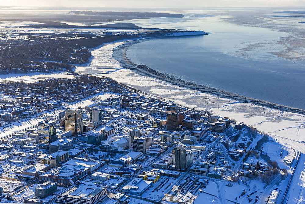 Aerial view of snow covering downtown Anchorage and Cook Inlet at low tide, the Hotel Captain Hook and Conoco Philips buildings in the foreground, Fire Island in the distance, South-central Alaska in winter, Anchorage, Alaska, United States of America