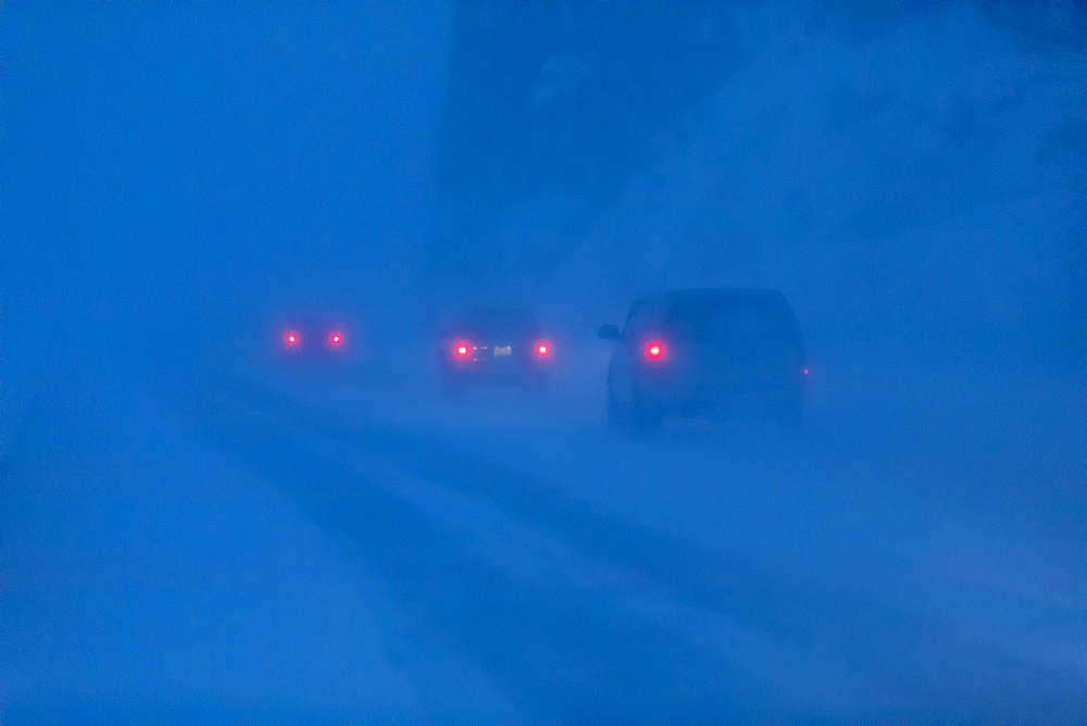 Car tail lights illuminate the blowing snow on the Seward Highway during a dark, winter night, Turnagain Arm, Kenai Peninsula, South-central Alaska, Alaska, United States of America