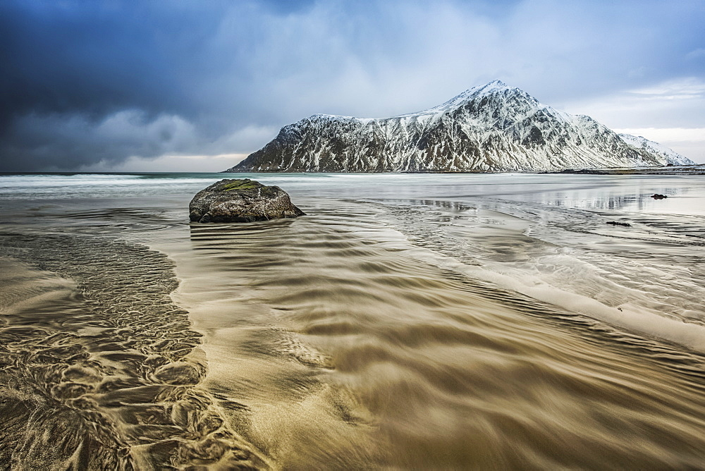 A landscape with rugged mountains and sand along the coastline under a cloudy sky, Nordland, Norway - 1116-48934