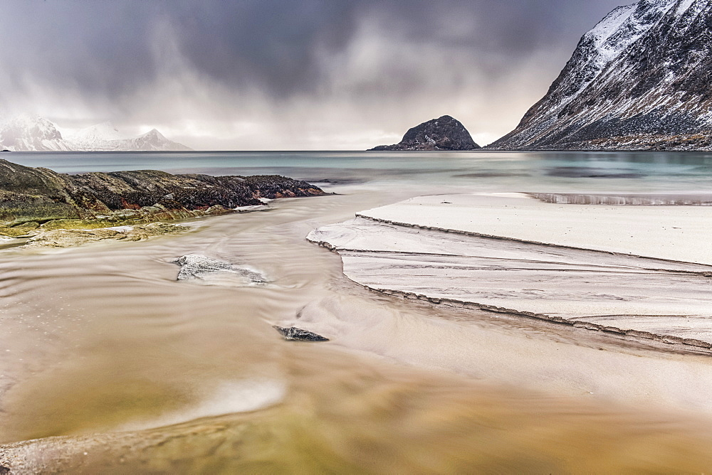 A landscape with rugged mountains and sand along the coastline under a cloudy sky, Nordland, Norway