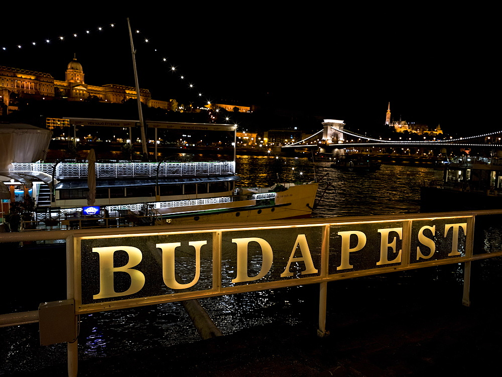 Szechenyi Chain Bridge over the Danube River and sign for Budapest illuminated at nighttime, Budapest, Budapest, Hungary