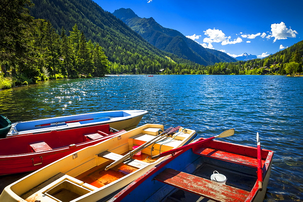 Colourful row boats with Champex Lake surrounded by mountains under blue sky, Alps, Champex, Switzerland