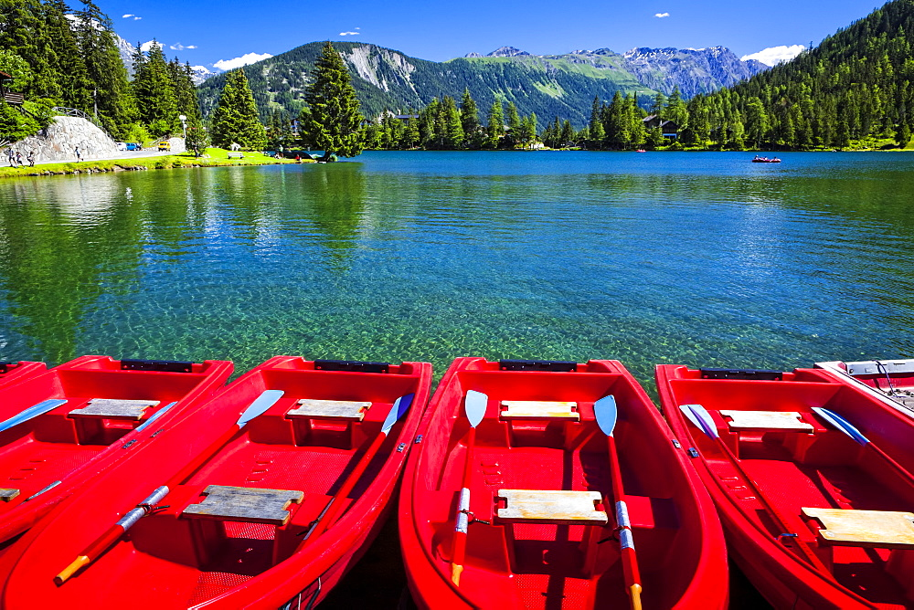 Red boats lined up at Champex Lake under blue sky with a mountain range in the background, Champex, Valais, Switzerland