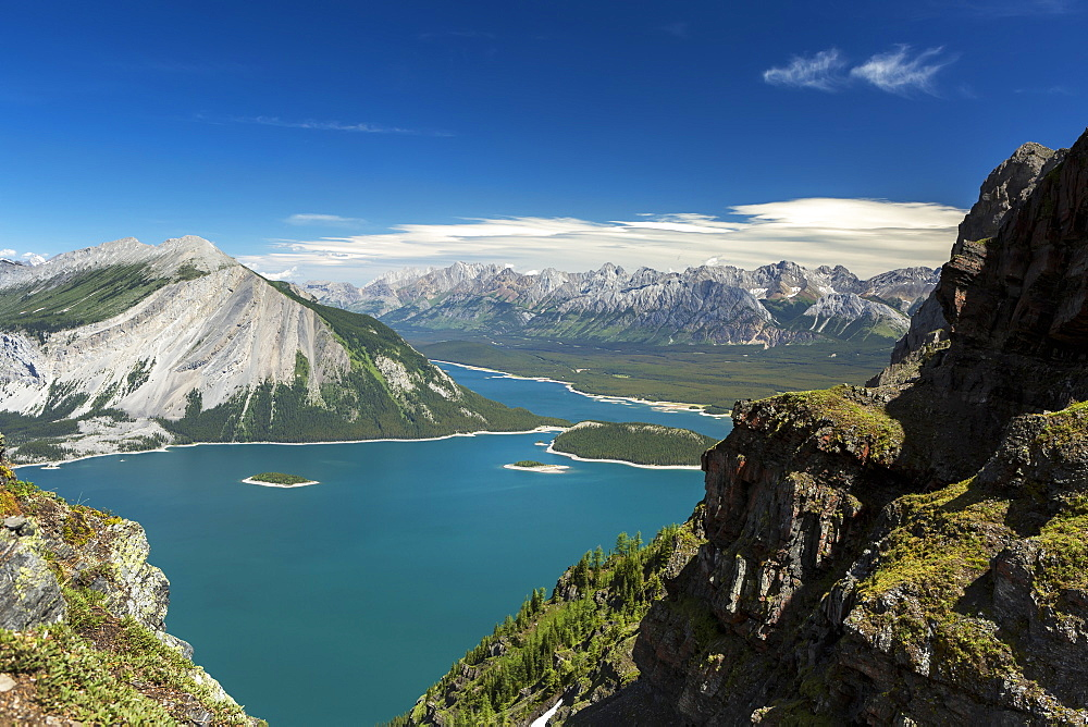 View from the top of mountain ridge looking down on colourful alpine lake and mountain range in the distance with blue sky and clouds, Kananaskis Country, Alberta, Canada