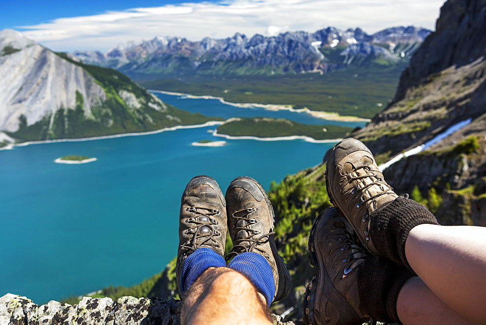 Close-up of a couple's hiking boots over a cliff overlooking a colourful alpine lake and mountain range in the distance, Kananaskis Country, Alberta, Canada