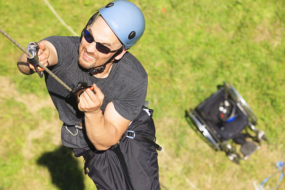 Man with spinal cord injury mountain climbing with adaptive equipment