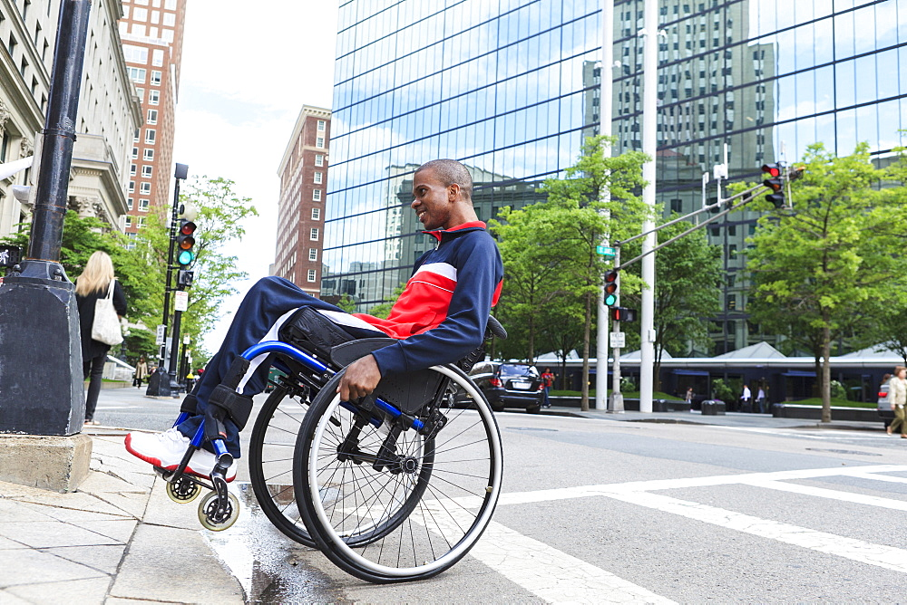 Man in wheelchair who had Spinal Meningitis going over a curb