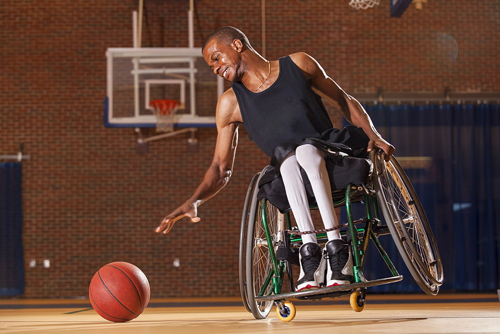 Man who had Spinal Meningitis in wheelchair reaching for basketball