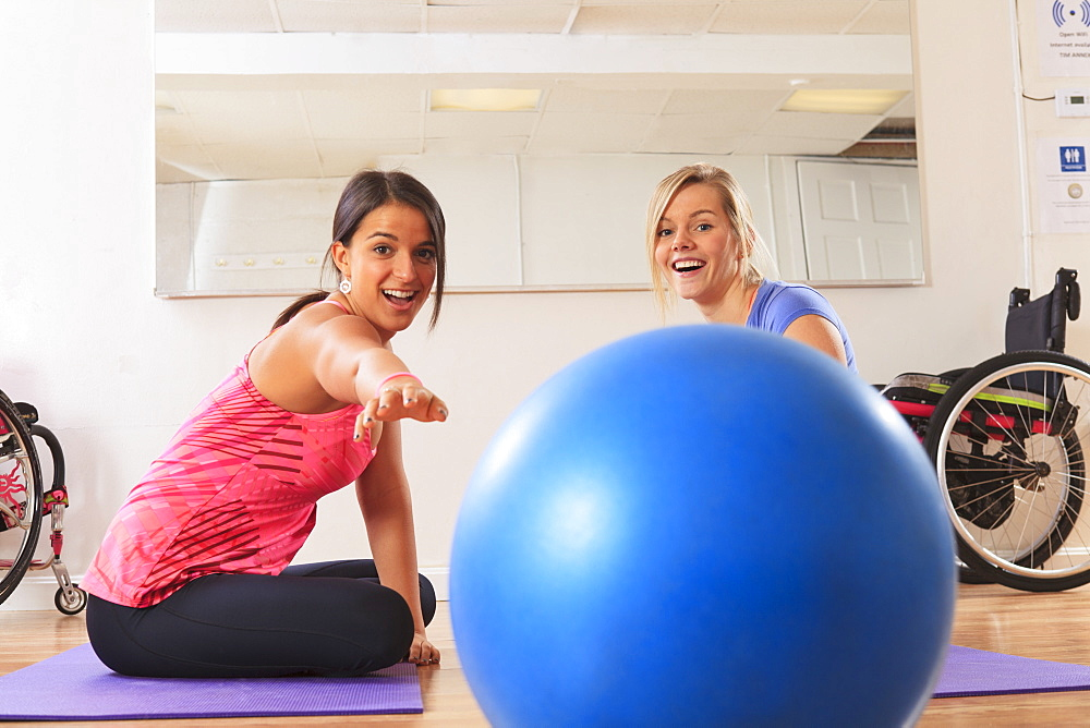 Young women with a spinal cord injuries playing with an exercise ball