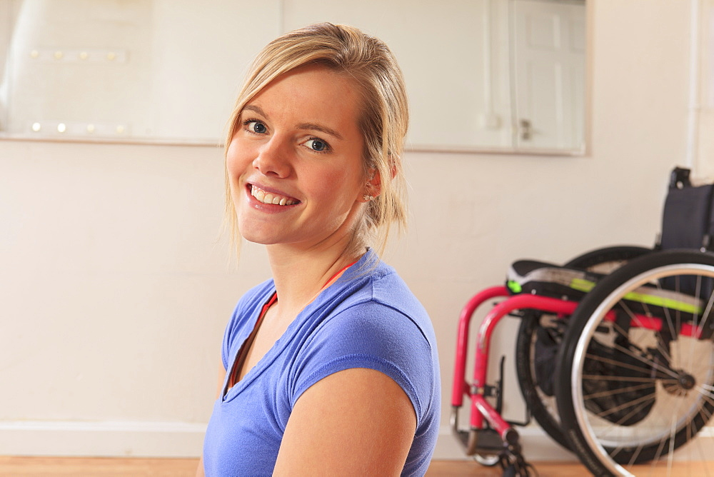 Young woman with a spinal cord injury with wheelchair in a yoga studio