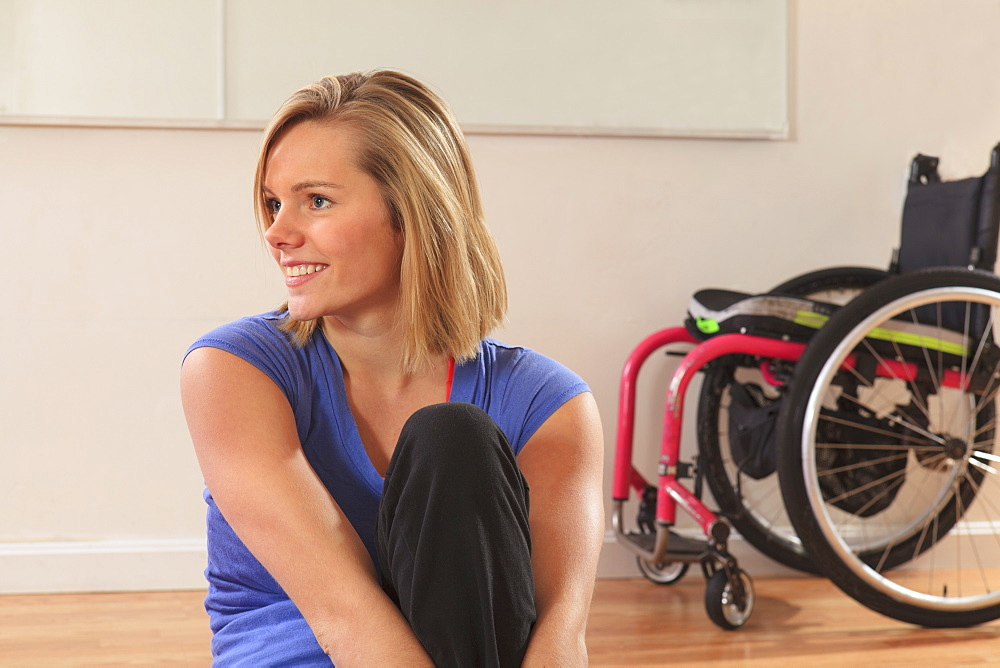 Portrait of a young woman with a spinal cord injury and her wheelchair in a yoga studio