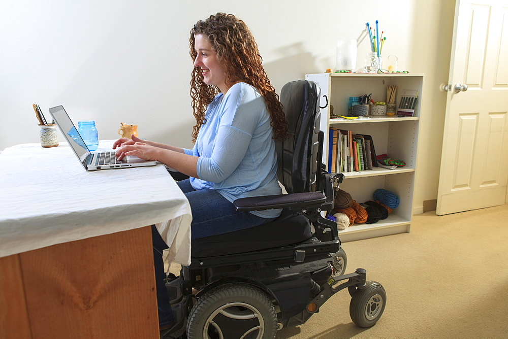 Woman with Muscular Dystrophy in her power chair using her laptop in her office