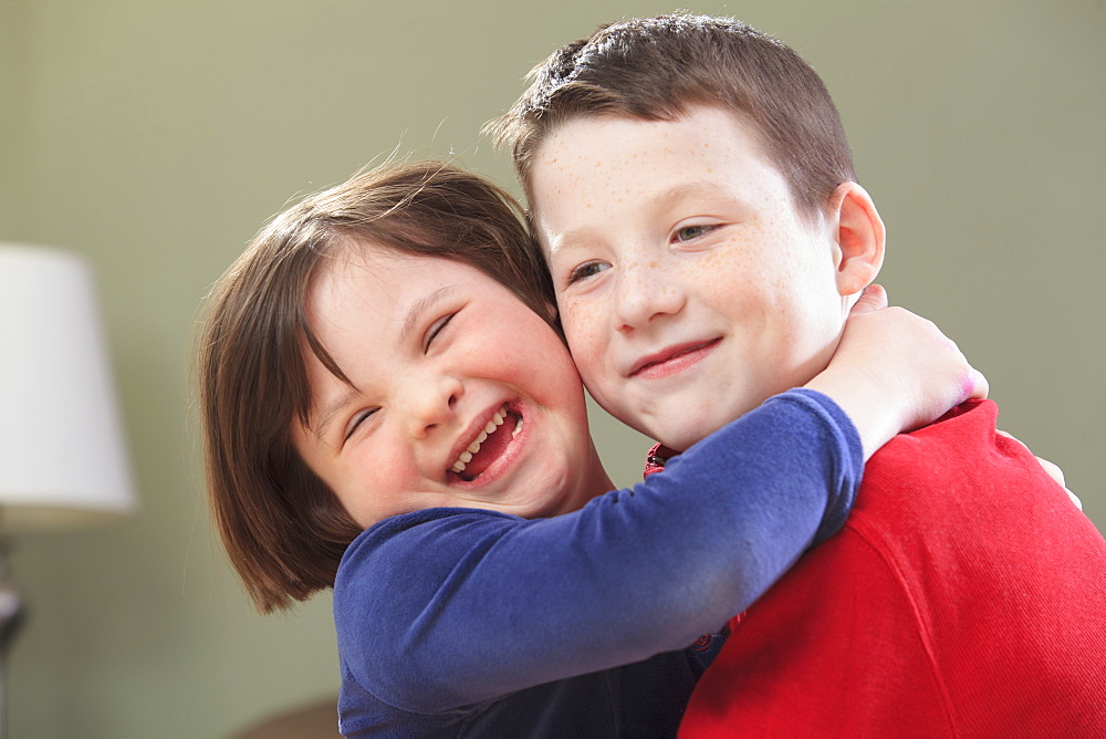 Little girl with Down Syndrome laughing with her brother
