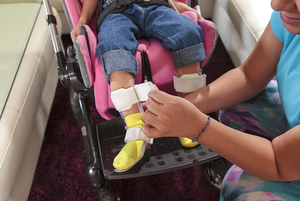 Mother putting leg brace on small daughter with Cerebral Palsy