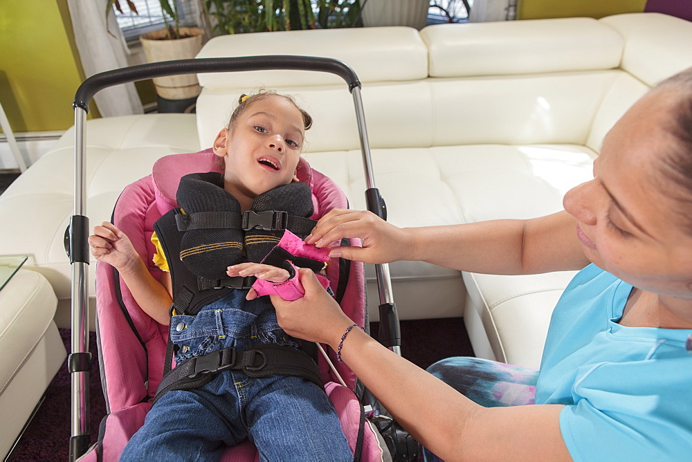 Mother putting hand brace on small daughter with Cerebral Palsy to go in stroller