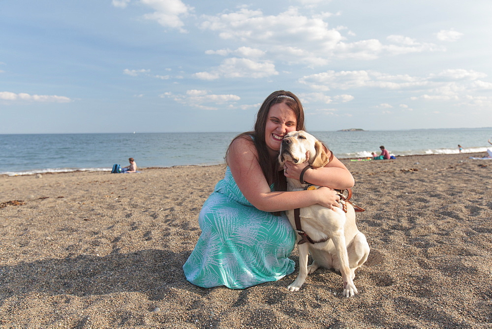 Young woman with visual impairment and her service dog hugging on the beach
