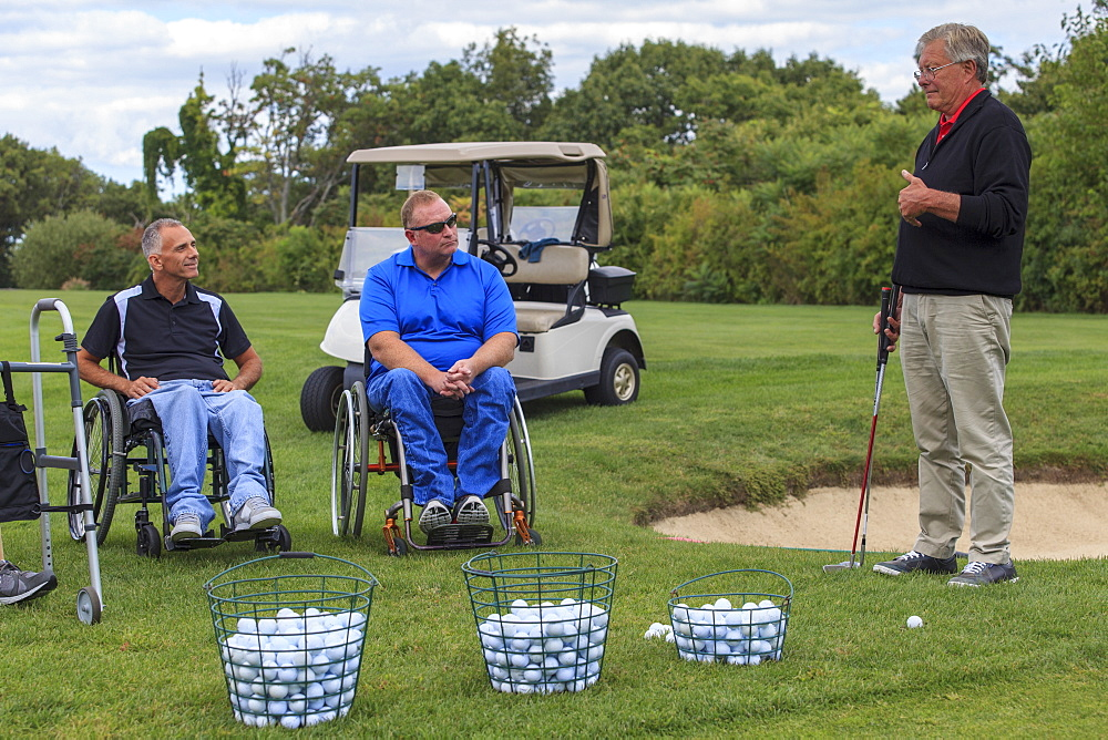 Two men in wheelchairs with spinal cord injuries learning golf from an instructor