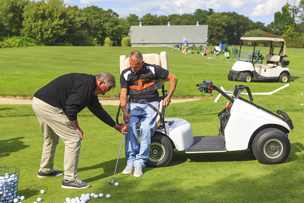 Man with spinal cord injury in an adaptive cart at golf putting green with an instructor
