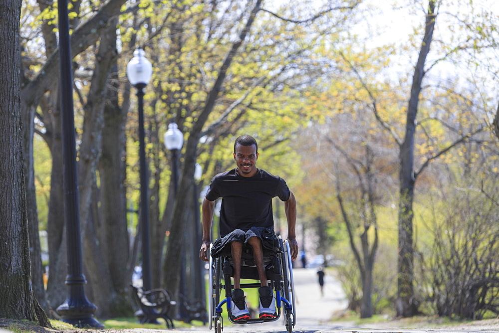 Man in a wheelchair who had Spinal Meningitis going through a park