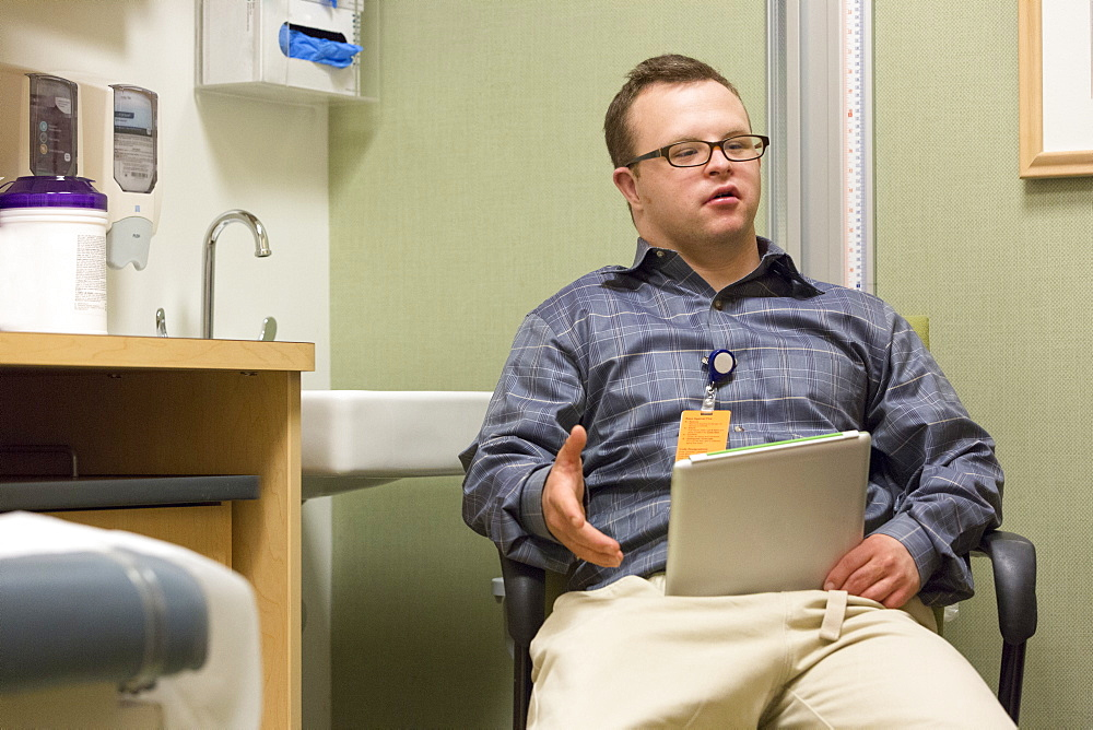 Hospital aid worker with Down Syndrome using a tablet in office - 1116-49872