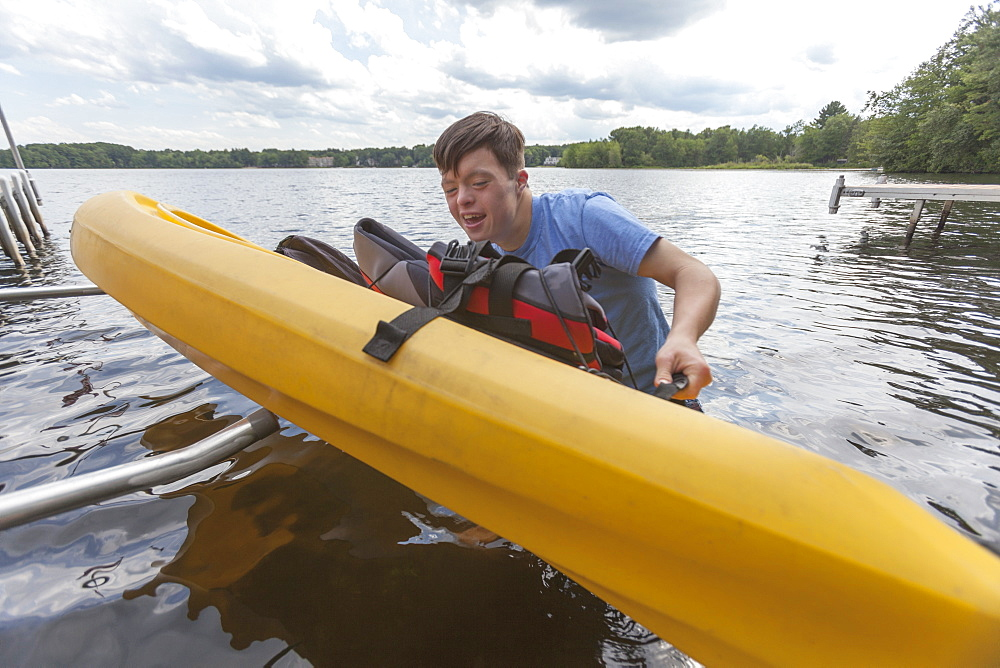 Young man with Down Syndrome preparing to use a kayak in a lake