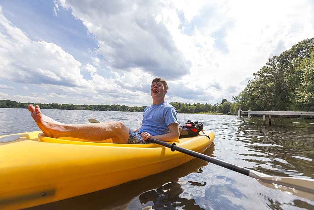 Happy young man with Down Syndrome rowing a kayak in a lake