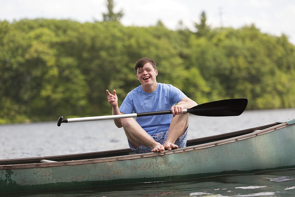 Happy young man with Down Syndrome rowing a canoe in a lake