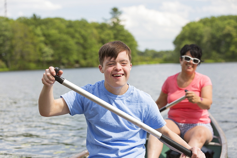 Young man with Down Syndrome rowing a canoe with his friend in a lake