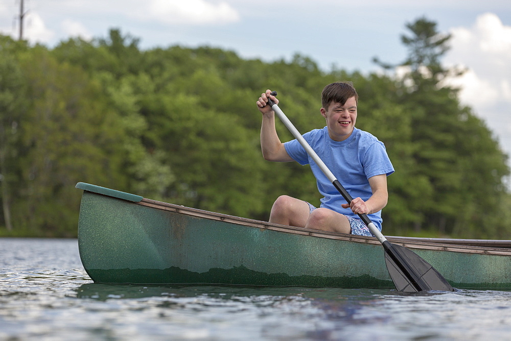 Young man with Down Syndrome rowing a canoe in a lake