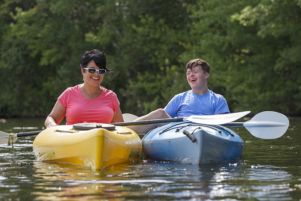 Young man with Down Syndrome kayaking with his friend in a lake