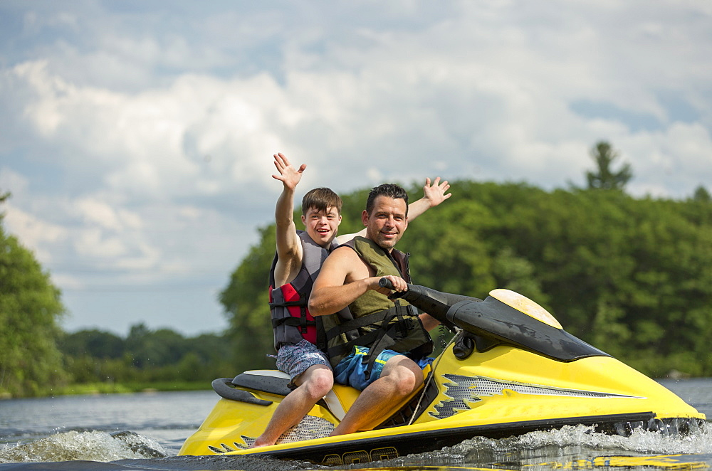 Young man with Down Syndrome riding on a jet ski with his friend in a lake