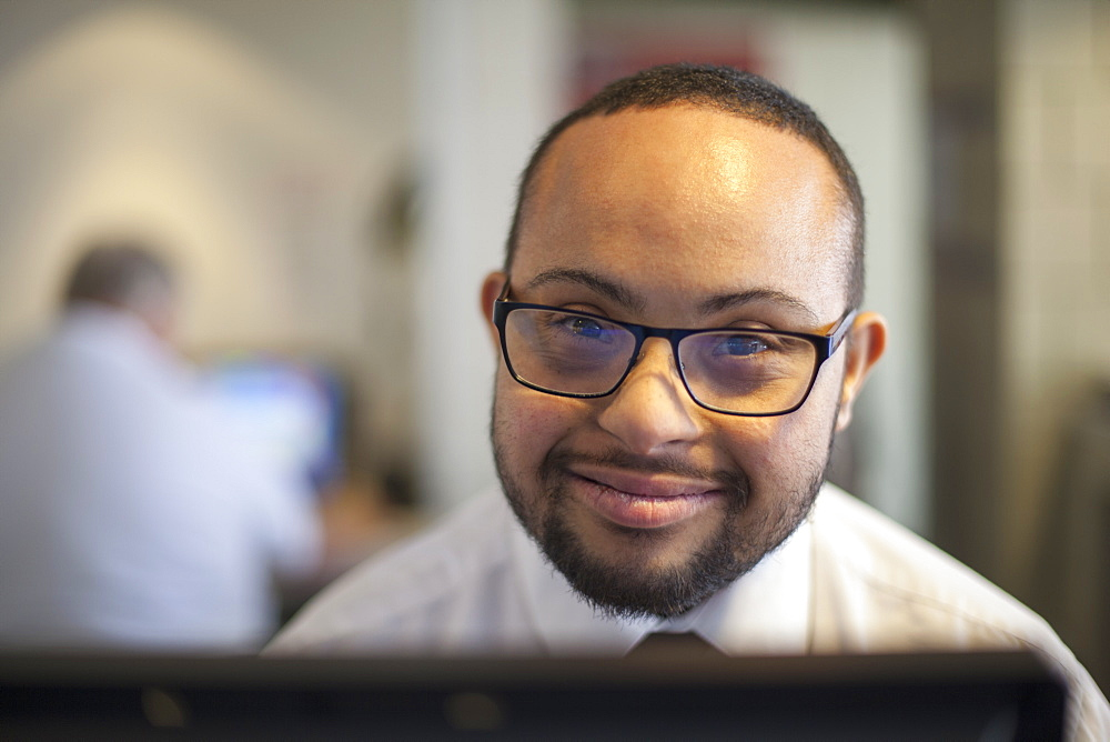 Happy African American man with Down Syndrome as a waiter taking reservations in the computer