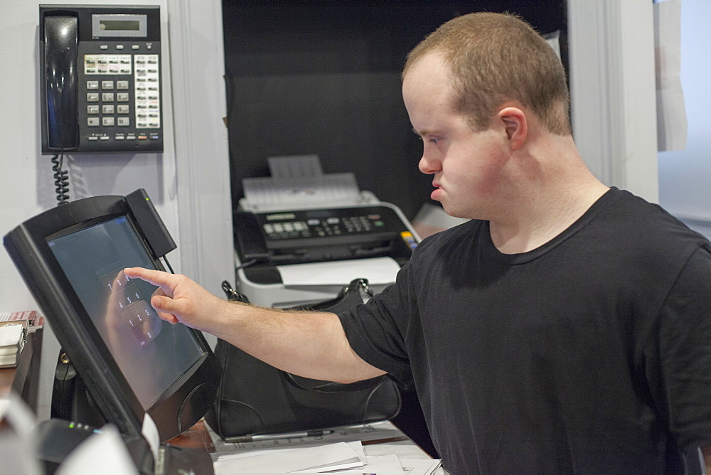 Waiter with Down Syndrome entering a sale on the computer in office