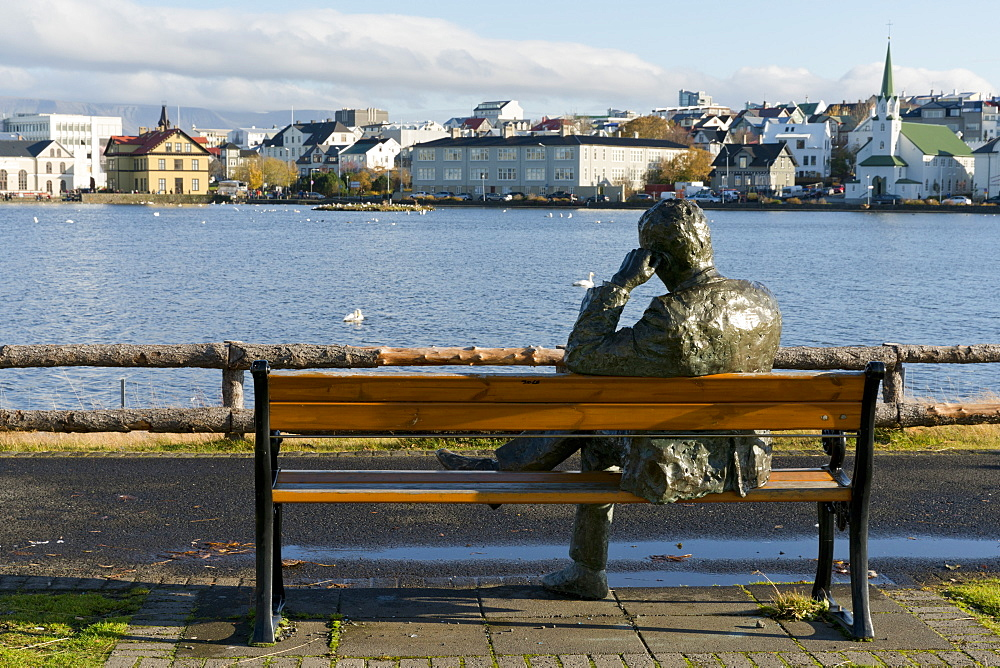 Sculpture of a man sitting on a park bench in front of Tjornin Lake and the Historic Centre of Rykjavik, Iceland, Polar Regions
