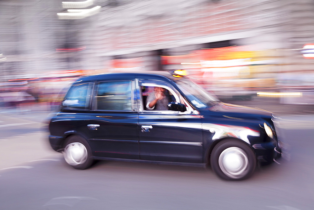 Motion blurred black taxi, Piccadilly Circus, London, England, United Kingdom, Europe