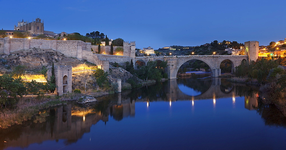 Puente de San Martin Bridge and San Juan des los Reyes Monastery reflected in the Tajo River, Toledo, Castilla-La Mancha, Spain, Europe