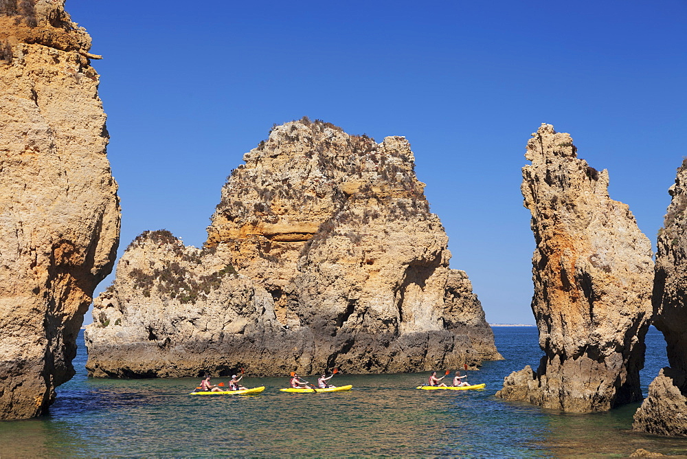 Kayaker exploring Ponta da Piedade Cape, near Lagos, Algarve, Portugal, Europe