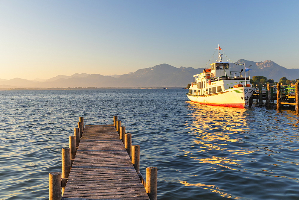 Excursion boat on a jetty at sunrise, Gstadt am Chiemsee, Lake Chiemsee, Upper Bavaria, Germany, Europe