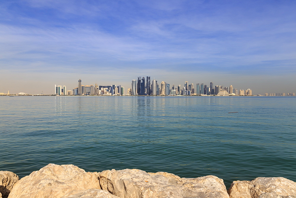 Modern city skyline of West Bay, across the calm turquoise waters of Doha Bay, from the Dhow Harbour, Doha, Qatar, Middle East