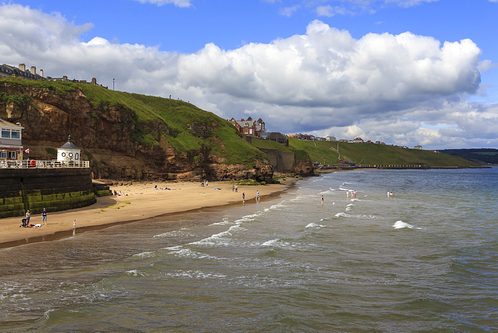 Bathers on West Cliff Beach, backed by grassy cliffs in summer, Whitby, North Yorkshire, England, United Kingdom, Europe