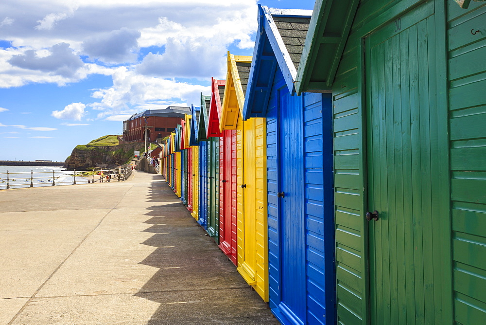 Row of colourful beach huts and their shadows, distant surfers in sea, West Cliff Beach, Whitby, North Yorkshire, England, United Kingdom, Europe