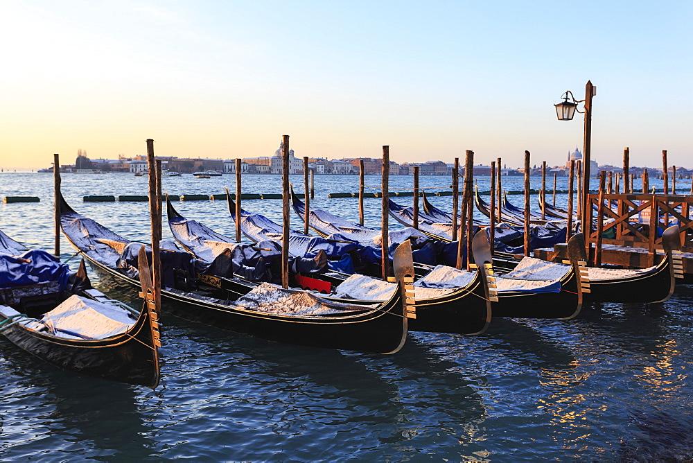 Gondolas covered in snow with view to La Guidecca, sunrise, Venice, UNESCO World Heritage Site, Winter, Veneto, Italy